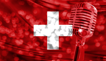 Microphone on a background of a blurry Switzerland flag close-up