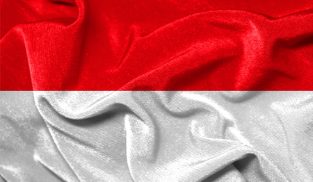 Realistic flag of Monaco on the wavy surface of fabric