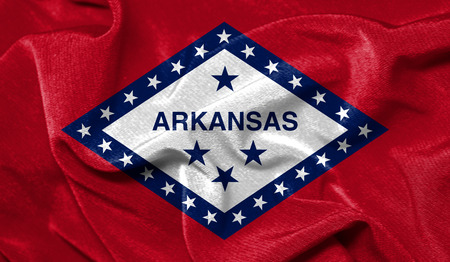 Realistic flag State of Arkansas on the wavy surface of fabric 免版税图像