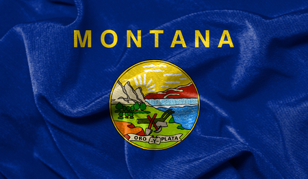Realistic flag State of Montana on the wavy surface of fabric 版權商用圖片