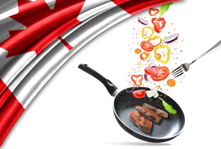 Frying pan with falling vegetables and meat, isolated. On the background of the flag of Canada Banco de Imagens
