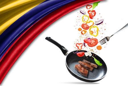 Frying pan with falling vegetables and meat, isolated. On the background of the flag of Colombia 写真素材