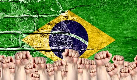 Male hands clenched in a fist raised up against the backdrop of a destroyed brick wall with a flag of Brazil. The concept of the labor movement from the people, the power and strength of civil society.