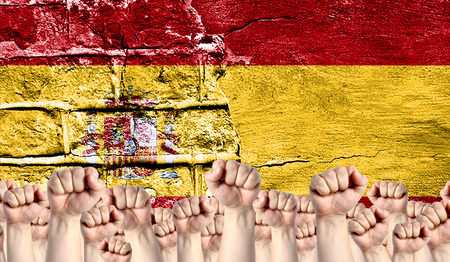 Male hands clenched in a fist raised up against the backdrop of a destroyed brick wall with a flag of Spain. The concept of the labor movement from the people, the power and strength of civil society.