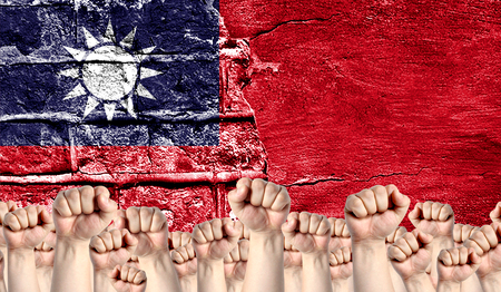Male hands clenched in a fist raised up against the backdrop of a destroyed brick wall with a flag of Taiwan. The concept of the labor movement from the people, the power and strength of civil society.