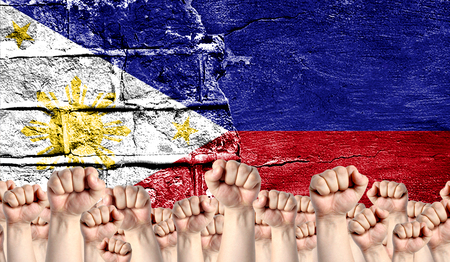 Male hands clenched in a fist raised up against the backdrop of a destroyed brick wall with a flag of Philippines. The concept of the labor movement from the people, the power and strength of civil society.