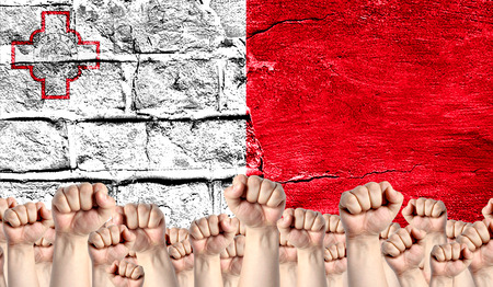 Male hands clenched in a fist raised up against the backdrop of a destroyed brick wall with a flag of malta. The concept of the labor movement from the people, the power and strength of civil society.