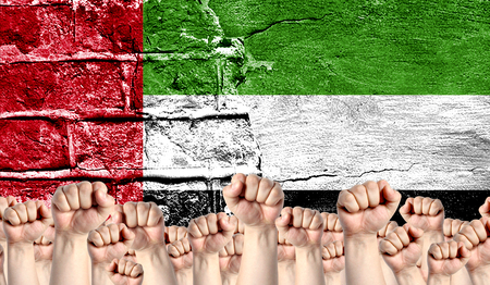 Male hands clenched in a fist raised up against the backdrop of a destroyed brick wall with a flag of United Arab Emirates. The concept of the labor movement from the people, the power and strength of civil society. Stock Photo