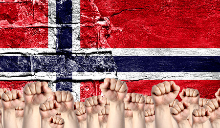 Male hands clenched in a fist raised up against the backdrop of a destroyed brick wall with a flag of Norway. The concept of the labor movement from the people, the power and strength of civil society. Stock Photo