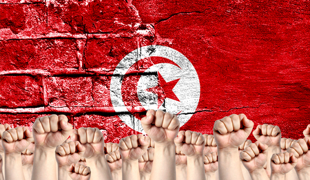 Male hands clenched in a fist raised up against the backdrop of a destroyed brick wall with a flag of Tunisia. The concept of the labor movement from the people, the power and strength of civil society.