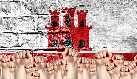 Male hands clenched in a fist raised up against the backdrop of a destroyed brick wall with a flag of Gibraltar. The concept of the labor movement from the people, the power and strength of civil society.