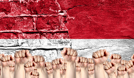 Male hands clenched in a fist raised up against the backdrop of a destroyed brick wall with a flag of Indonesia. The concept of the labor movement from the people, the power and strength of civil society.