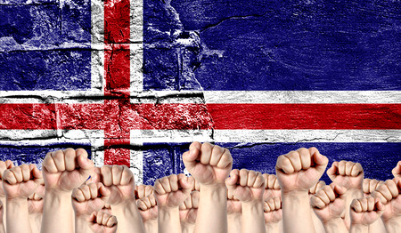 Male hands clenched in a fist raised up against the backdrop of a destroyed brick wall with a flag of Iceland. The concept of the labor movement from the people, the power and strength of civil society.