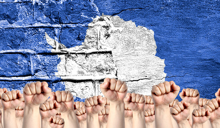 Male hands clenched in a fist raised up against the backdrop of a destroyed brick wall with a flag of Antarctic. The concept of the labor movement from the people, the power and strength of civil society.
