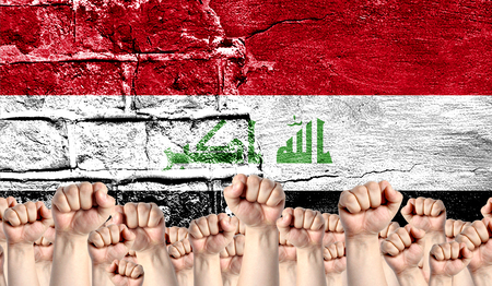 Male hands clenched in a fist raised up against the backdrop of a destroyed brick wall with a flag of Iraq. The concept of the labor movement from the people, the power and strength of civil society.