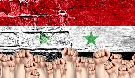 Male hands clenched in a fist raised up against the backdrop of a destroyed brick wall with a flag of Syria. The concept of the labor movement from the people, the power and strength of civil society.