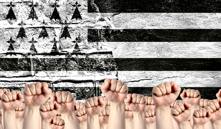 Male hands clenched in a fist raised up against the backdrop of a destroyed brick wall with a flag of Brittany. The concept of the labor movement from the people, the power and strength of civil society.