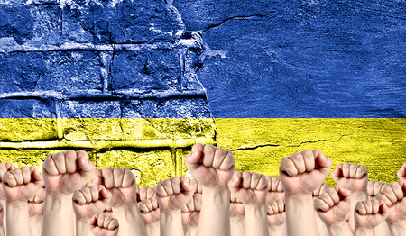 Male hands clenched in a fist raised up against the backdrop of a destroyed brick wall with a flag of Ukraine. The concept of the labor movement from the people, the power and strength of civil society.