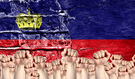 Male hands clenched in a fist raised up against the backdrop of a destroyed brick wall with a flag of Liechtenstein. The concept of the labor movement from the people, the power and strength of civil society.