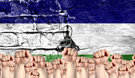 Male hands clenched in a fist raised up against the backdrop of a destroyed brick wall with a flag of Lesotho. The concept of the labor movement from the people, the power and strength of civil society. Stock Photo