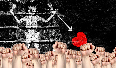 Male hands clenched in a fist raised up against the backdrop of a destroyed brick wall with a flag of Blackbeard Pirate. The concept of the labor movement from the people, the power and strength of civil society.