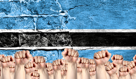 Male hands clenched in a fist raised up against the backdrop of a destroyed brick wall with a flag of Botswana. The concept of the labor movement from the people, the power and strength of civil society. Stock Photo