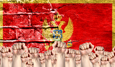 Male hands clenched in a fist raised up against the backdrop of a destroyed brick wall with a flag of Montenegro. The concept of the labor movement from the people, the power and strength of civil society.