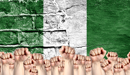 Male hands clenched in a fist raised up against the backdrop of a destroyed brick wall with a flag of Nigeria. The concept of the labor movement from the people, the power and strength of civil society.