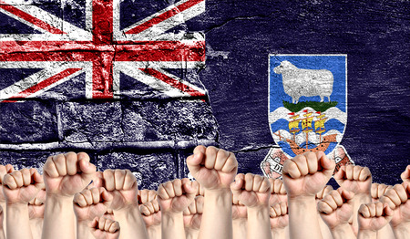 Male hands clenched in a fist raised up against the backdrop of a destroyed brick wall with a flag of Falkland Islands. The concept of the labor movement from the people, the power and strength of civil society.
