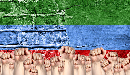 Male hands clenched in a fist raised up against the backdrop of a destroyed brick wall with a flag of Dagestan. The concept of the labor movement from the people, the power and strength of civil society.