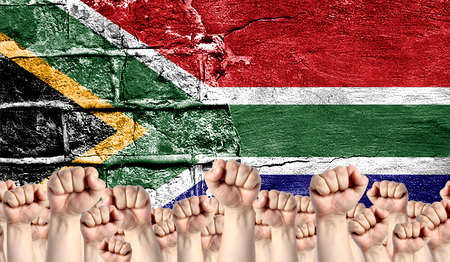 Male hands clenched in a fist raised up against the backdrop of a destroyed brick wall with a flag of South Africa. The concept of the labor movement from the people, the power and strength of civil society. Stock Photo