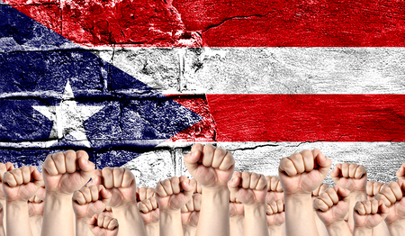 Male hands clenched in a fist raised up against the backdrop of a destroyed brick wall with a flag of Puerto Rico. The concept of the labor movement from the people, the power and strength of civil society.