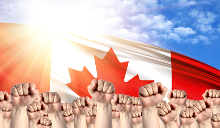 Labor Day concept with fists of men against the background of the flag of Canada