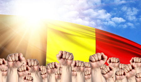 Labor Day concept with fists of men against the background of the flag of Belgium