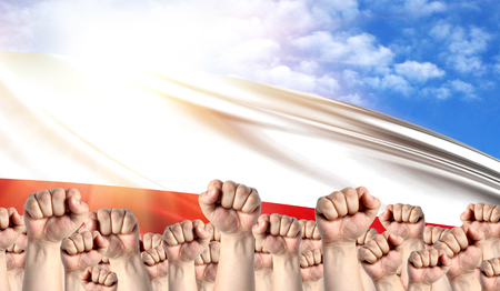 Labor Day concept with fists of men against the background of the flag of Poland Stock Photo
