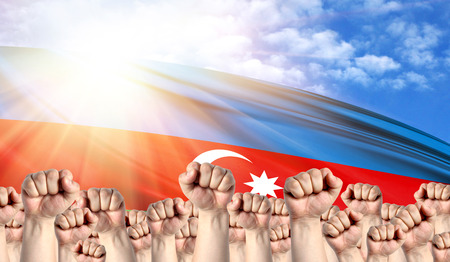 Labor Day concept with fists of men against the background of the flag of Azerbaijan