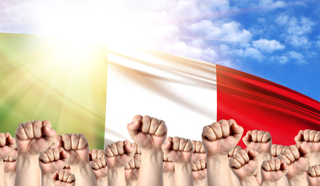 Labor Day concept with fists of men against the background of the flag of Italy Stock Photo