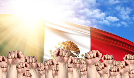 Labor Day concept with fists of men against the background of the flag of Mexico