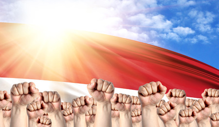 Konzept zum Tag der Arbeit mit Fäusten von Männern vor dem Hintergrund der Flagge Indonesiens