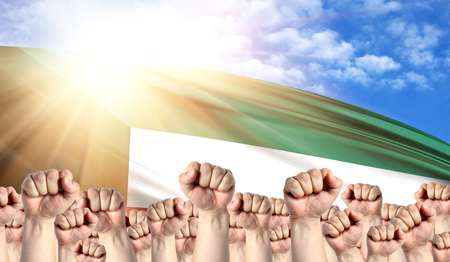 Labor Day concept with fists of men against the background of the flag of Kuwait