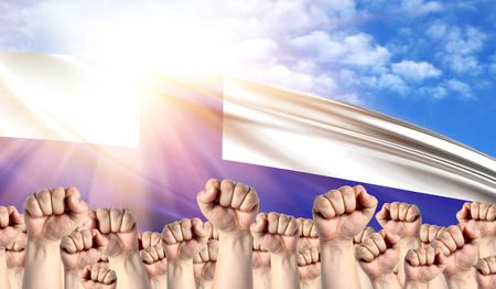 Labor Day concept with fists of men against the background of the flag of Finland