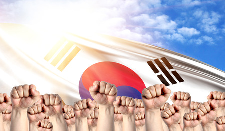 Labor Day concept with fists of men against the background of the flag of South Korea
