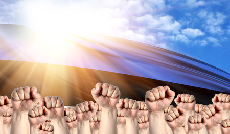 Labor Day concept with fists of men against the background of the flag of Estonia