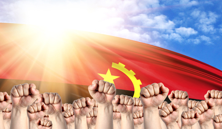 Labor Day concept with fists of men against the background of the flag of Angola