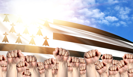 Labor Day concept with fists of men against the background of the flag of Brittany Stock Photo