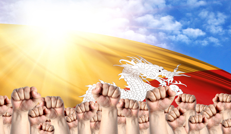 Labor Day concept with fists of men against the background of the flag of Butane