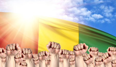 Labor Day concept with fists of men against the background of the flag of Guinea Stock Photo