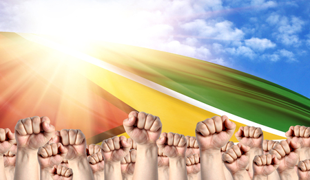 Labor Day concept with fists of men against the background of the flag of Guyana