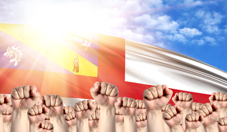 Labor Day concept with fists of men against the background of the flag of Herm