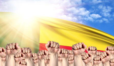 Labor Day concept with fists of men against the background of the flag of Benin